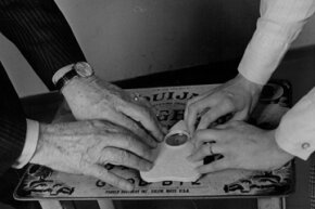 Two people play the Ouija board in 1972. The basic design has not changed in more than 100 years.