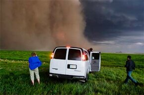 Tour guests dash back to the van as the changing sky takes a turn for the worse during a Tempest Tours storm chasing tour across the Great Plains of the U.S. in 2006.