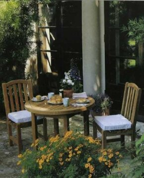The simple teak furnishings suit the patio's small scale and harmonize with the soft gray shades.