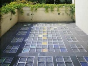 This enclosed patio pairs flagstone with contrasting colored glass, specially coated to reflect light.