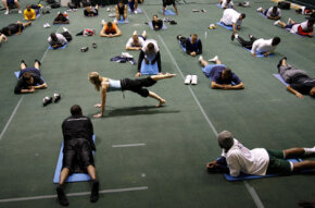 Professional Football players practice Pilates with an instructor.
