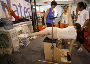 A woman in Beijing tries to figure out a Pilates exercise machine at a fitness expo.