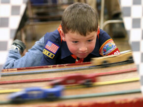 Seven-year-old Carter Pompola watches cars race by him during the annual Cub Scout Pack 136 Pinewood Derby Race at Indian Paintbrush Elementary School in Laramie, Wyo., March 29, 2008.