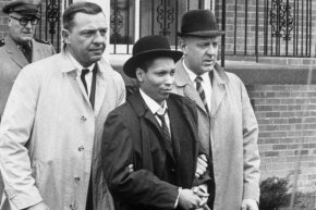 Kitty Genovese's killer, Winston Moseley, is led away in handcuffs on March 21, 1968, after escaping police custody while serving a life sentence for her death.