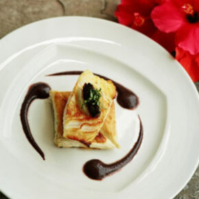 Simple elegance is achieved here following three key plating techniques -- wide-rimmed white plate, stacking and decorative sauce placement.
