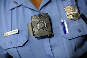 Washington D.C. Metropolitan Police Officer Debra Domino models a body camera that officers can attach to their uniforms on Sept. 24, 2014.