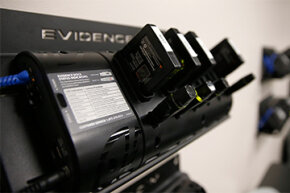 Body cameras and their batteries are docked for charging and downloading video in a patrol room.