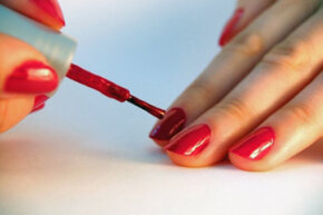 Iron oxides and other pigments in red nail polish can potentially stain the nails underneath.