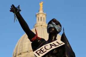 A sign touting the recall of Wisconsin governor Scott Walker hangs on a statue in front of the state capitol building in Madison in March 2011, amid protests against Walker's bill denying collective bargaining rights to public workers.