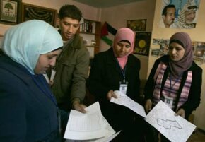 Employees from the Palestinian statistics department check forms to be used for the Palestinian population census during house-to-house visits in the West Bank city of Ramallah, December 2007.