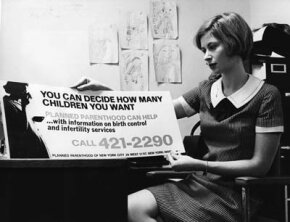 In December 1967, birth control information, which was to be displayed on New York buses, is held up for scrutiny by Marcia Goldstein, the publicity director of Planned Parenthood.