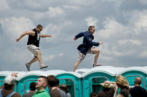 Two men dash across the tops of porta-potties in the infield at the Kentucky Derby at Churchill Downs, 2008. The porta-potty race is an unofficial Kentucky Derby tradition.