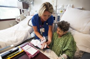 A nurse uses chlorhexidine gluconate bath wipes on an elderly patient at a Florida hospital. Some hospitals have found the wipes to be handy in protecting ICU patients from MRSA infections.