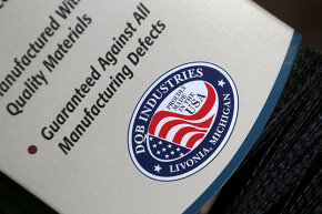 """A """"proudly made in the USA"""" logo is seen on the packaging of a brush produced at Detroit Quality Brushes in Livonia, Michigan. Not all companies that display this logo really  make their products in America."""