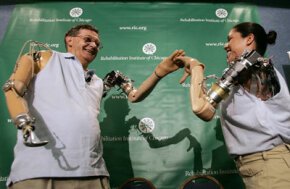 Jesse Sullivan (left) and Claudia Mitchell (right) high-five each other as they demonstrate the functionality of their thought-controlled bionic arms during a news conference in Washington, D.C.