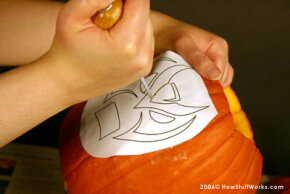 Use a sharp tool to transfer the stencil to the pumpkin's surface.