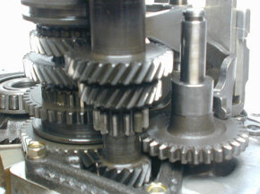 Most of the gears in a manual transmission have helical teeth. The three gears that make up reverse have straight teeth. The large spur gear on the right slides up to put the car in reverse.