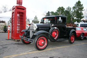 Two examples of some of the vintage pieces sold by the Red Baron: a cast iron phone booth from London and a 1930s Ford Pickup.