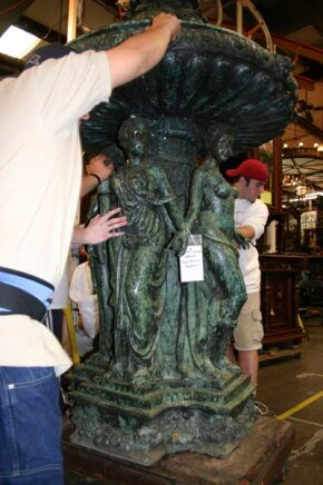 Two of Red Baron's crew move a sculpture to the auction floor.