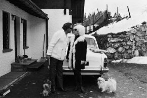 Richard Burton with wife Elizabeth Taylor on a winter sports holiday, surrounded by their precious pooches.