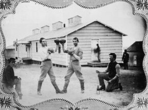 Two pugilists touch gloves outside their barracks, circa 1865