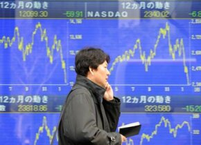 A pedestrian passes before a share prices board in Tokyo, Jan. 22, 2008.