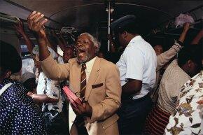 A preacher holds an impromptu service on a train going between Soweto and Johannesburg.