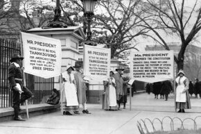 Several demonstrators dressed as pilgrims carry placards calling for the release of political prisoners in front of the White House, ca. 1919.