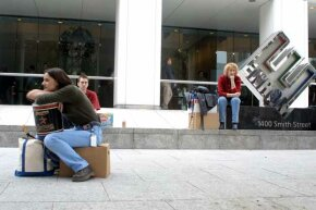Meredith Stewart (left), who worked at Enron, sits on her personal belongings in front of the company's headquarters after being laid off in 2001.