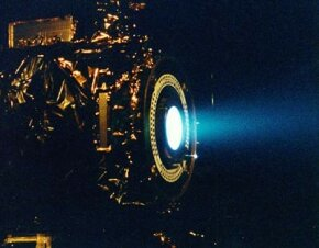 This image of a xenon ion engine, photographed through a port of the vacuum chamber where it was being tested at NASA's Jet Propulsion Laboratory, shows the faint blue glow of charged atoms being emitted from the engine. The ion propulsion engine is the first non-chemical propulsion to be used as the primary means of propelling a spacecraft.
