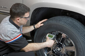 A Goodwrench technician checks the wheels and tires with a Tire Pressure Monitoring Systems (TPMS) tool.