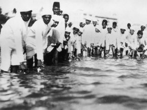 Young Nationalist supporters of Mahatma Gandhi break salt laws by filling containers with sea water in Bombay, India