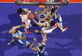 Mark Jones of the University of Dayton Flyers rebounds the ball amidst the defense of the University of Tulsa Golden Hurricanes during the first round of the NCAA Tournament on March 20, 2003, in Spokane, Wash.