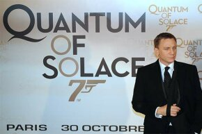 Actor Daniel Craig poses in front of a poster for the James Bond film 'Quantum of Solace.' The title means a really small amount of comfort.