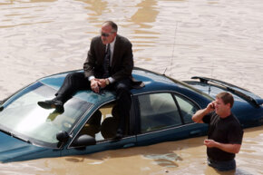 Castle Rock Police Department investigator Tim Gorman sits on top of his flooded-out police car waiting for Denver firefighters to rescue him from a highway just after a major rainstorm in 2002.