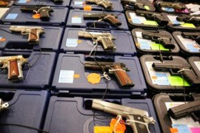 An assortment of Colt and Glock semi-automatic handguns on display at the Nations Gunshow in Chantilly, Virginia, 2009. See more pictures of guns.