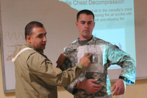 Senior medical officer and commander Maj. Adnan Najji explains the technique for applying a needle chest decompression using Spc. Christopher Graham, a brigade medic and health specialist. Senior medics are often in charge of teaching other medics.