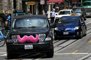 """A Lyft car, with its trademark pink """"mustache,"""" drives along Powell Street in San Francisco, in June 2014. Lyft is a service where people use their own cars to transport strangers for pay."""
