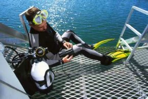 A diver tries on an electronic shark repellent unit, which sends out an electrical field in the water to repel sharks.