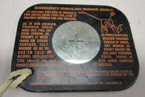 The reverse of an emergency signaling mirror issued to pilots for use in the 1940s. Note the instructions on how to use it.