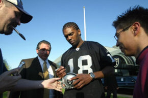 Former Oakland Raiders wide receiver Randy Moss greets fans after his 2005 introductory press conference. The team restructured his salary to include a prorated signing bonus spread out over the length of his contract.