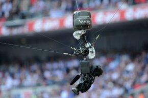 """Skycam装备用凯夫拉尔增强绳索卷悬挂在行动上方。""""border="""