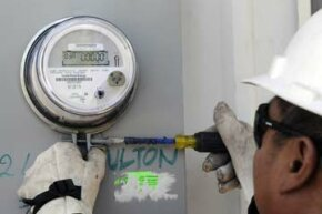 A Houston, Texas utility worker installs a smart meter for CenterPoint Energy on June 5, 2009. The utility company, which serves 2.2 million customers in the metropolitan area, expects to spend $1 billion on smart grid technology.