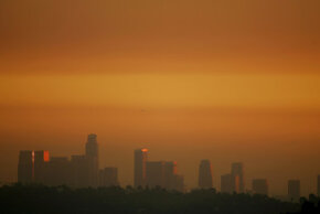The skyline of downtown Los Angeles is lit up by the murky browns and reds of a smoggy sunset.