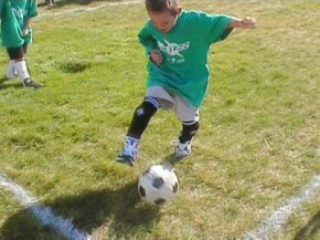 A young player dribbles the ball