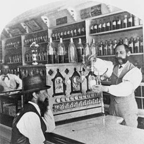 At this small-town soda fountain in the 1890s, a pharmacist whips up a fizzy concoction for a customer.