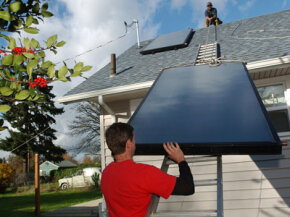 The owner of a solar energy company installs panels for a hot water system in Oregon.