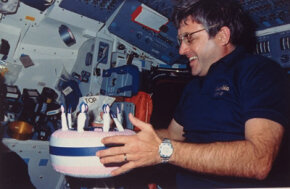 Sometimes space food isn't even food: Astronaut Daniel Brandenstein holds up inflatable cake in honor of his 47th birthday aboard the Space Shuttle Columbia.
