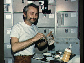 Skylab 3 Astronaut Owen Garriott reconstitutes food in the crew quarters.