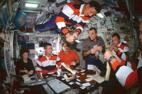 Crews from three different countries have a meal together at the International Space Station, 2001.